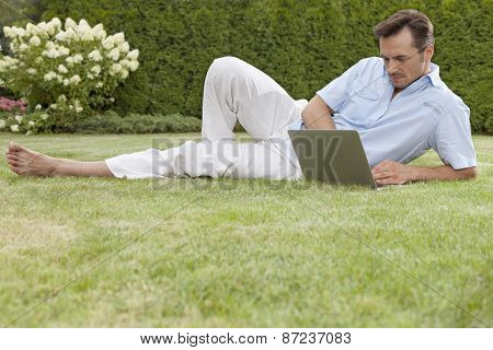 Full length of young man working on laptop in park