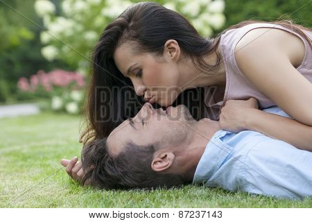 Side view of young woman kissing man while lying in park