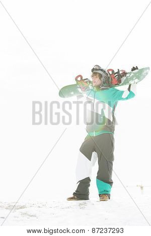 Full length of young man carrying snowboard in snow