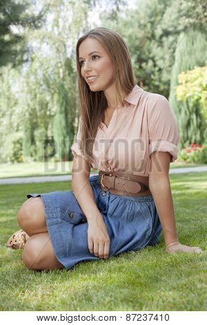 Beautiful young woman looking away while relaxing on grass in park