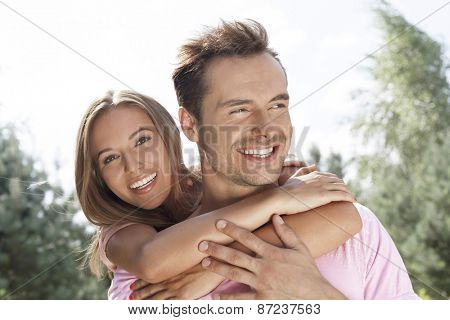 Portrait of beautiful young woman embracing man in summer park