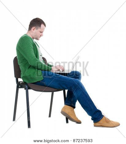 Side view of a man sitting on a chair to study with a laptop. Isolated  over white background