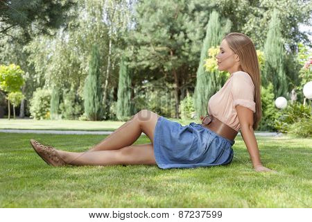 Full length side view of beautiful young woman relaxing on grass in park