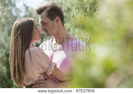 Side view of young romantic couple in park