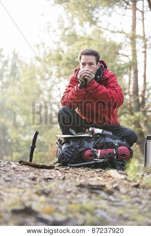 Male backpacker warming hands while looking away in forest