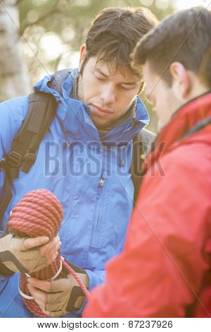 Male hikers looking at rope in forest