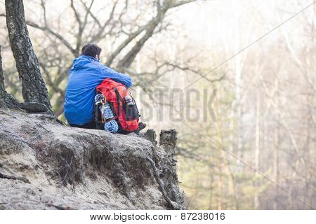 Rear view of hiker with backpack sitting on edge of cliff in forest