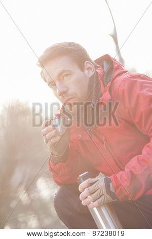 Male hiker having coffee in forest