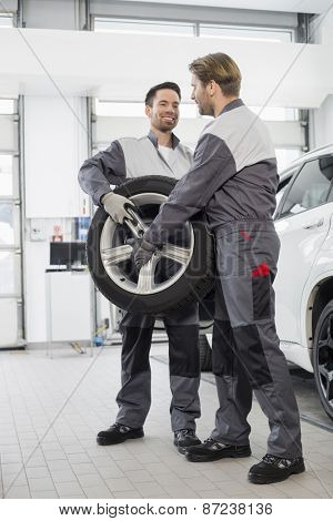 Full-length of maintenance engineers carrying tire in car workshop
