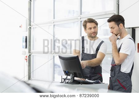 Male automobile mechanics conversing in repair shop