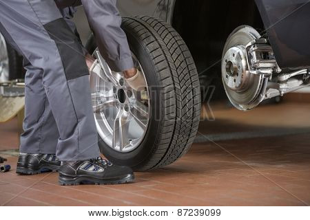 Low section of repairman fixing car's tire in repair shop