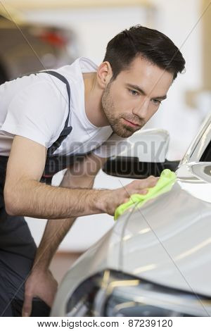 Young maintenance engineer cleaning car in repair shop