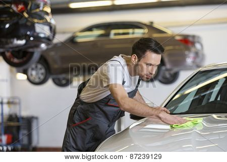 Young male mechanic cleaning car in repair shop