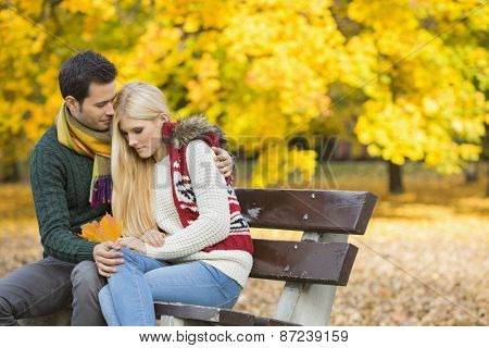 Loving young man hugging shy woman on park bench during autumn