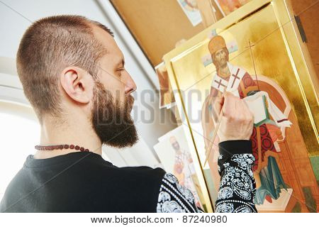 Religious icon painter man paints a new icon with brush at workshop