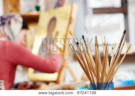 Iconography. brushes heap with woman painting the Mother of God icon on background