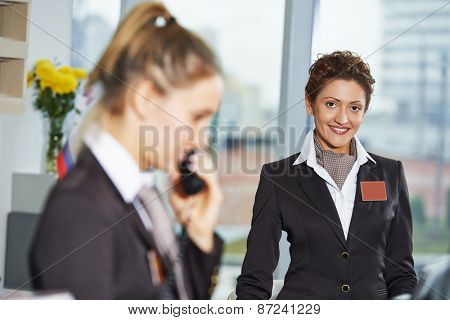 female receptionist workers standing at hotel counter