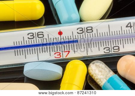 a clinical thermometer and tablets. symbolic photo for flu and colds