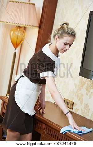 Hotel service. female housekeeping worker cleaning table from dust in room