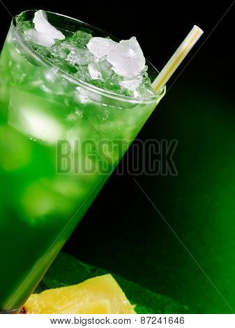 Green drink  with straw and ice on dark background. Top view. Glass tilted