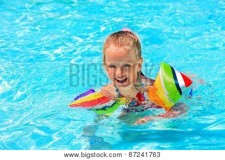 Child with armbands play in swimming pool. Summer outdoor.