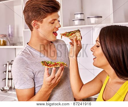 Young happy family cooking pizza and feed each other at kitchen.