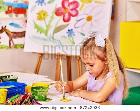 Child painting at easel in school. Kids pictures.