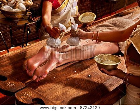 Young woman having feet Ayurveda India spa massage.