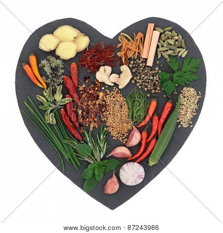 Herb and spice selection on heart shaped slate over white background.
