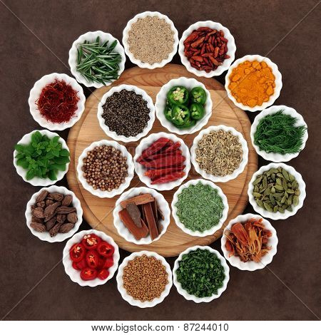 Large herb and spice selection in porcelain crinkle bowls on wooden board.