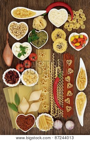 Italian pasta and mediterranean food ingredients forming an abstract background over oak.