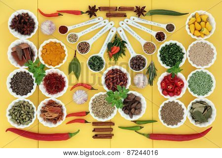 Herb and spice selection in measuring spoons, crinkle bowls and loose over wooden yellow background.