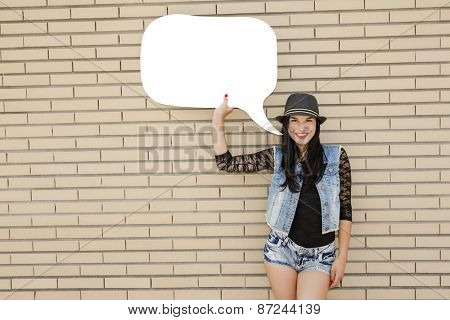 Beautiful and young teenager holding a thought balloon, in front of a brick wall