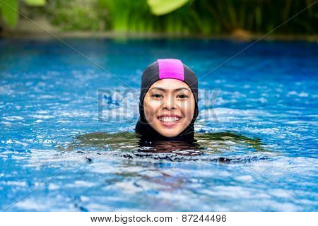 Muslim woman or girl swimming in pool at tropical garden wearing Burkini halal swimwear