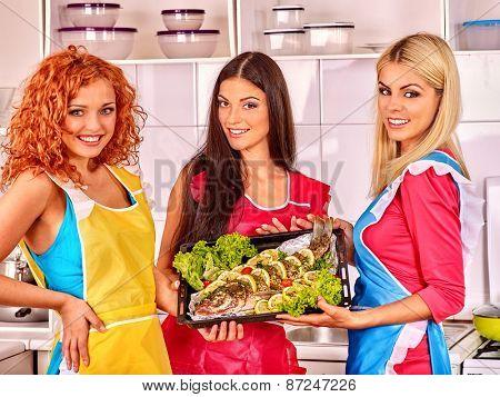 Happy women prepare fish in oven.