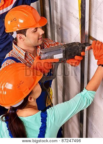Happy family in builder uniform indoor. Drilled wall