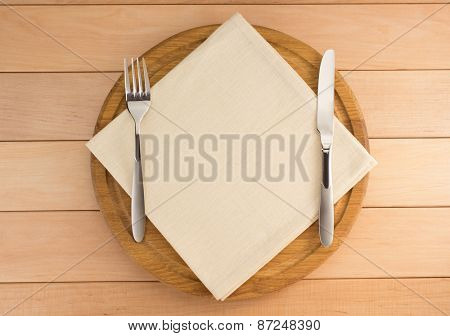 kitchen utensils and napkin at cutting board on wood
