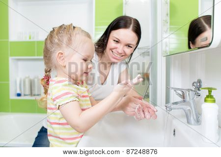 Happy Mother And Child Washing Hands With Soap Together