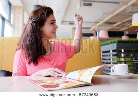 Young woman calls up the waiter in the restaurant