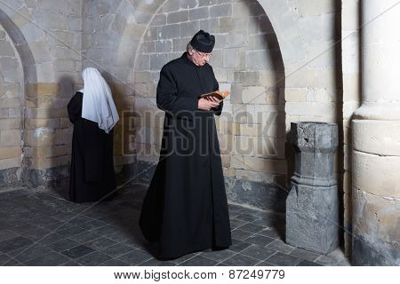 Priest passing a young nun along the walls of a medieval abbey