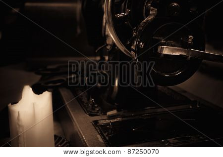 Old Sewing Machine, Fabric And Rusty Scissors At The Light Candle. Side View, Sepia, Low Key