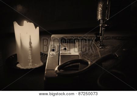 Old Sewing Machine, Fabric And Rusty Scissors At The Light Candle. Close Up,  Sepia, Low Key
