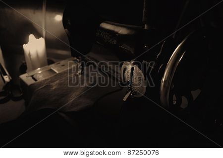Handwheel Old Sewing Machine, Fabric And Tailoring Scissors In The Light Burning Candle. Sepia, Low