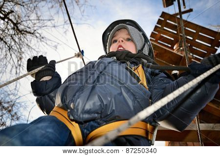 Little Boy Going On Suspension Way In The Equipment And Looking Down. Close Up, Horizontal, Shot Fro