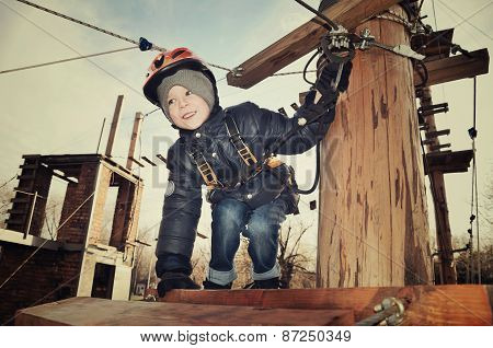 Tinted Image Smiling Boy Sits On Suspension Bridge And Looking Away. Horizontal