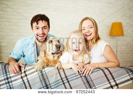 Parents, their daughter and dog staying at home