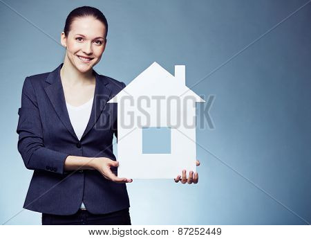 Cheerful female realtor showing paper house