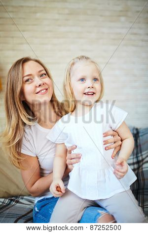 Happy little girl sitting on the mother knees