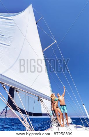 Happy couple in honeymoon vacation in luxury sea cruise, enjoying each other and travel on beautiful sailboat, looking up in the sky
