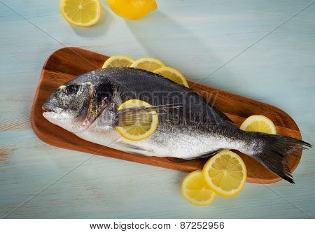 Raw Sea Bream With Lemon On  A Wooden Cutting Board.
